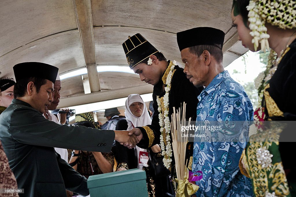 Moh Nasrodin (C), a groom, says his wedding vows inside a lorry train during a mass wedding ceremony on December 12, 2012 in Yogyakarta, Indonesia. Twelve couples participated in a mass wedding as today saw a surge in marriage across the globe to mark the once in a century date of 12/12/12.