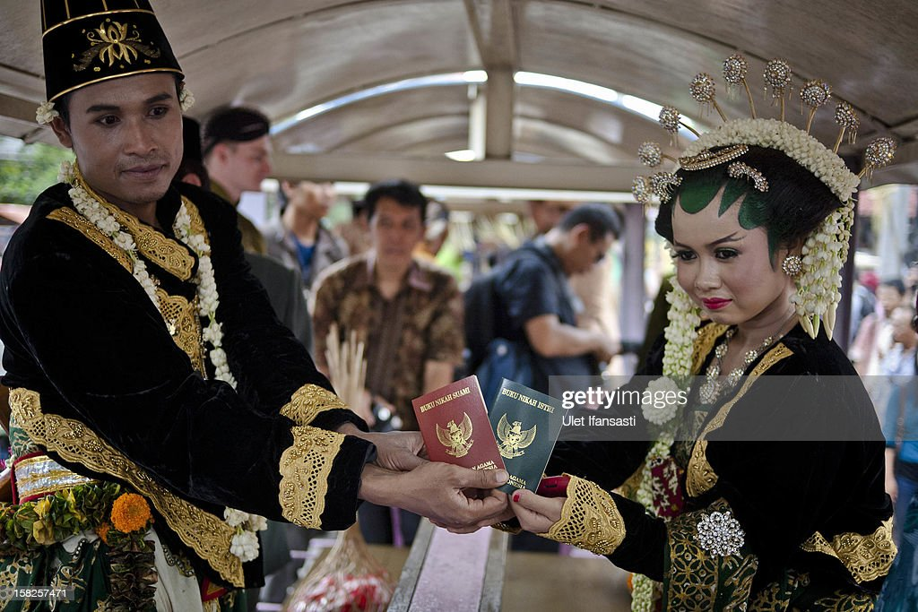 Moh Nasrodin and Meisaroh, show their marriage certificates inside a lorry train during a mass wedding ceremony on December 12, 2012 in Yogyakarta, Indonesia. Twelve couples participated in a mass wedding as today saw a surge in marriage across the globe to mark the once in a century date of 12/12/12.