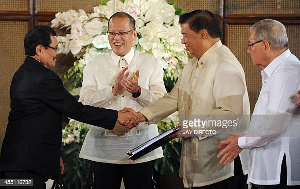 Mohager Iqbal chief peace negotiator of the Moro Islamic Liberation Front hands over the draft of the Bangsamoro basic law to Senate President...