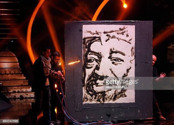 Mohamad Al Diri paints a portrait of late Palestinian leader Yasser Arafat using a blowtorch during the final episode of the panArab TV program...