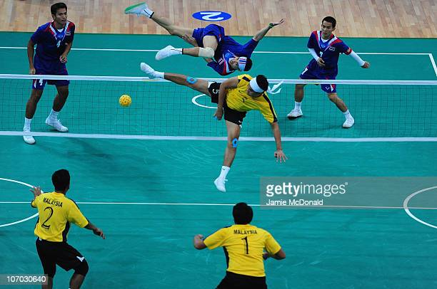 Mohamad Futra Abd Ghani of Malaysia tries to block Anuwat Chaichana of Thailand in the Men's Sepaktakraw Team Final at Haizhu Sports Centre during...