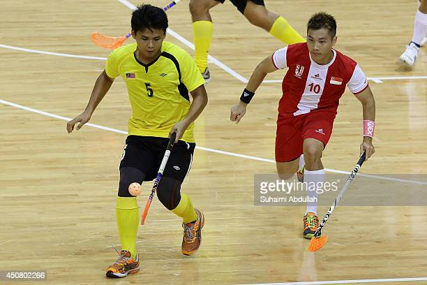 Mohamad Hanif Abdul Malik of Malaysia and Cheong Zhi Xian Brandon of Singapore chase for the ball during the World University Championship Floorball...