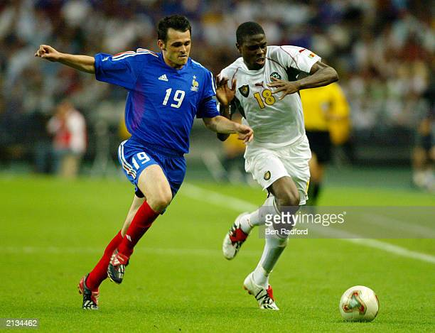 Mohamadou Idrissou of Cameroon reaches the ball ahead of Willy Sagnol of France during the FIFA Confederations Cup Final between France and Cameroon...