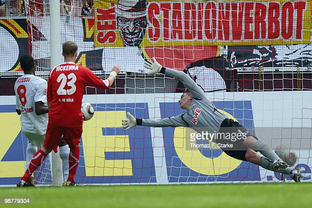 Mohamadou Idrissou of Freiburg scores his teams first goal against Kevin McKenna and Faryd Mondragon of Cologne during the Bundesliga match between 1...