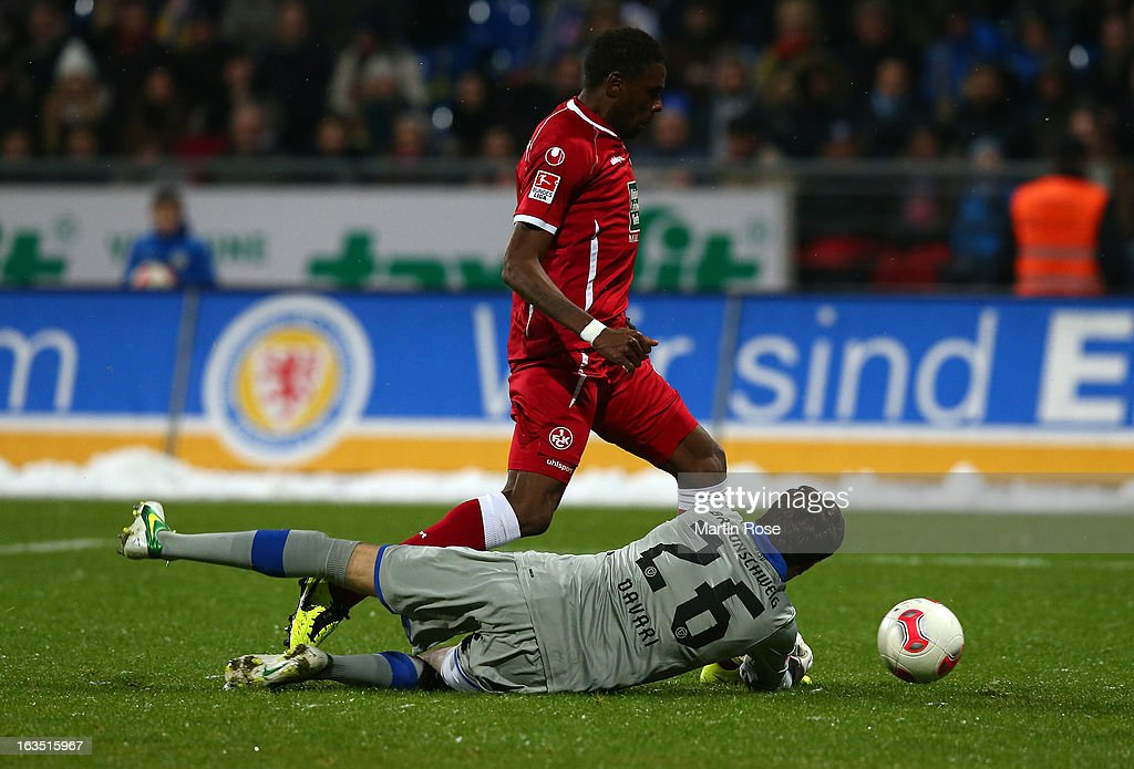 Mohamadou Idrissou (back) of Kaiserslautern fails to score over Daniel Davari, goalkeeper of Braunschweig during the second Bundesliga match between Eintracht Braunschweig and 1. FC Kaiserslautern at Eintracht Stadium on March 11, 2013 in Braunschweig, Germany.