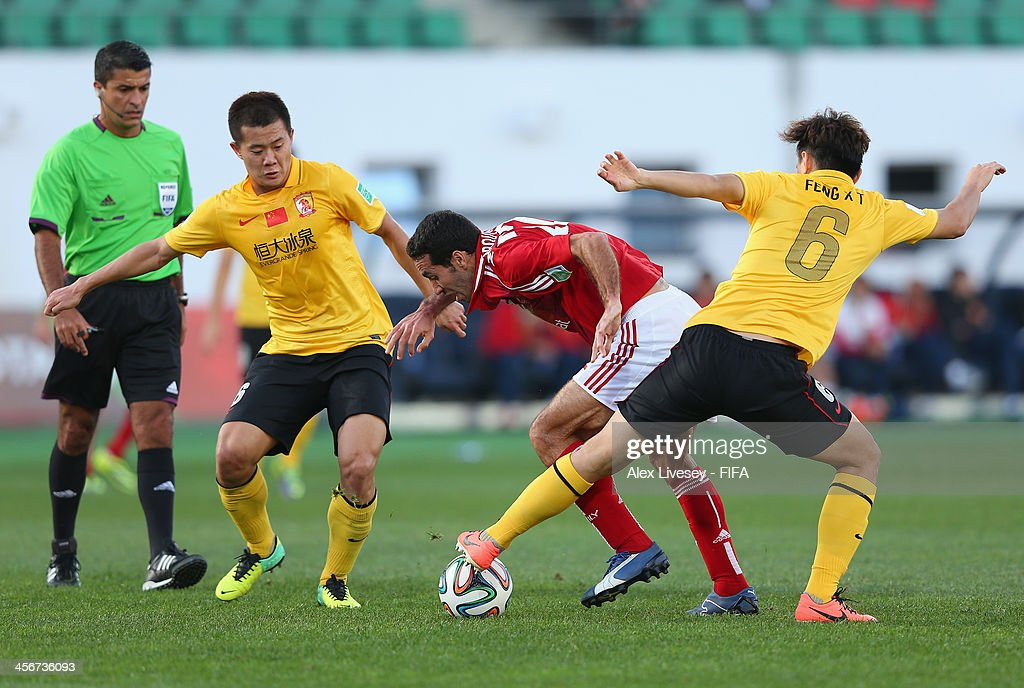 <a gi-track='captionPersonalityLinkClicked' href=/galleries/search?phrase=Mohamed+Aboutrika&family=editorial&specificpeople=4081123 ng-click='$event.stopPropagation()'>Mohamed Aboutrika</a> of Al-Ahly SC is tackled by <a gi-track='captionPersonalityLinkClicked' href=/galleries/search?phrase=Xiaoting+Feng&family=editorial&specificpeople=2333049 ng-click='$event.stopPropagation()'>Xiaoting Feng</a> of Guangzhou Evergrande FC during the FIFA Club World Cup Quarter Final match between Guangzhou Evergrande FC and Al-Ahly SC at the Agadir Stadium on December 14, 2013 in Agadir, Morocco.