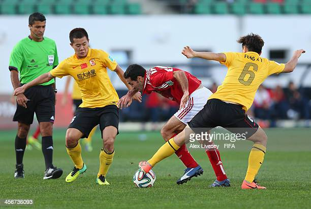Mohamed Aboutrika of AlAhly SC is tackled by Xiaoting Feng of Guangzhou Evergrande FC during the FIFA Club World Cup Quarter Final match between...