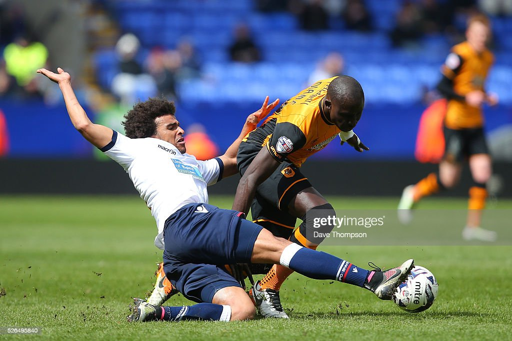 Mohamed Diame of Hull City is tackled by Derik Osede of Bolton Wanderers during the Sky Bet Championship match between Bolton Wanderers and Hull City at the Macron Stadium on April 30, 2016 in Bolton, United Kingdom.