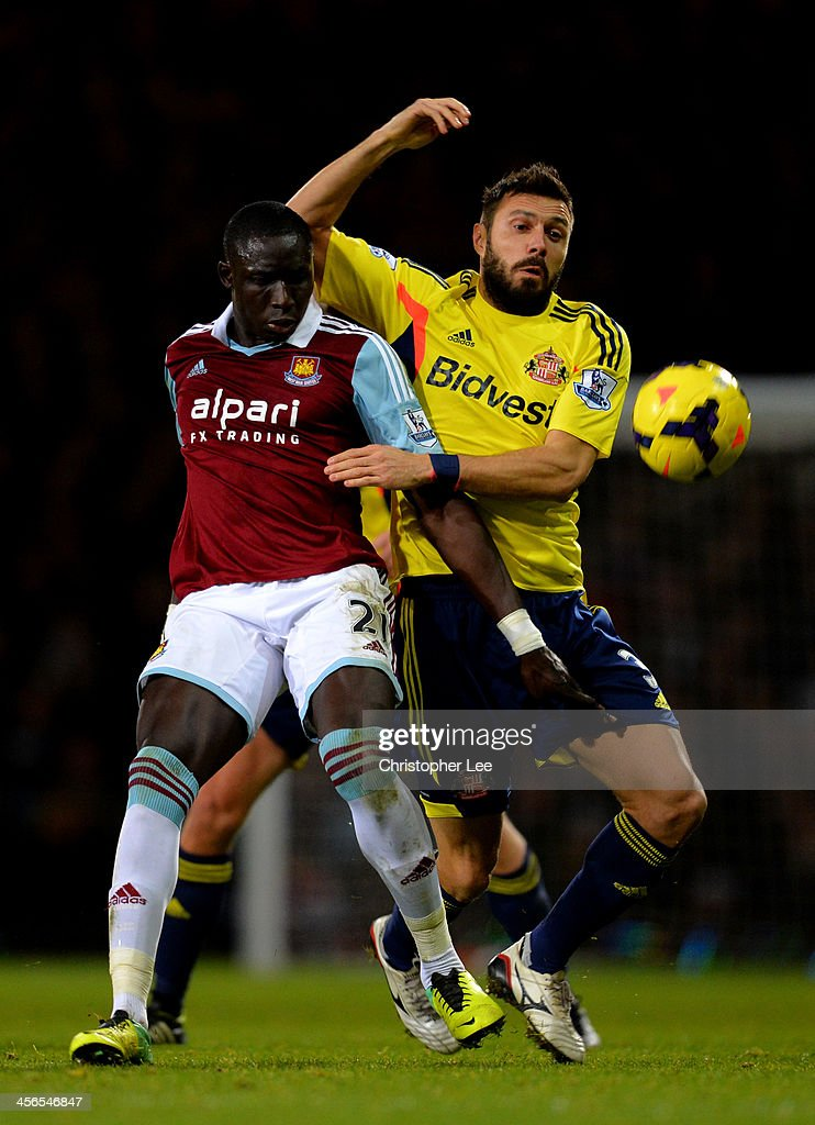 Mohamed Diame of West Ham holds off the challenge from <a gi-track='captionPersonalityLinkClicked' href=/galleries/search?phrase=Andrea+Dossena&family=editorial&specificpeople=709826 ng-click='$event.stopPropagation()'>Andrea Dossena</a> of Sunderland during the Barclays Premier League match between West Ham United and Sunderland at Boleyn Ground on December 14, 2013 in London, England.