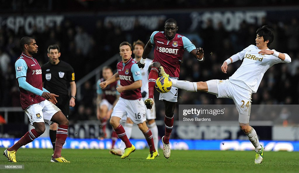 Mohamed Diame of West Ham United (L) and Ki Sung-Yeung of Swansea City (R) challenge for the ball during the Barclays Premier League match between West Ham United and Swansea at the Boleyn Ground on February 2, 2013 in London, England.
