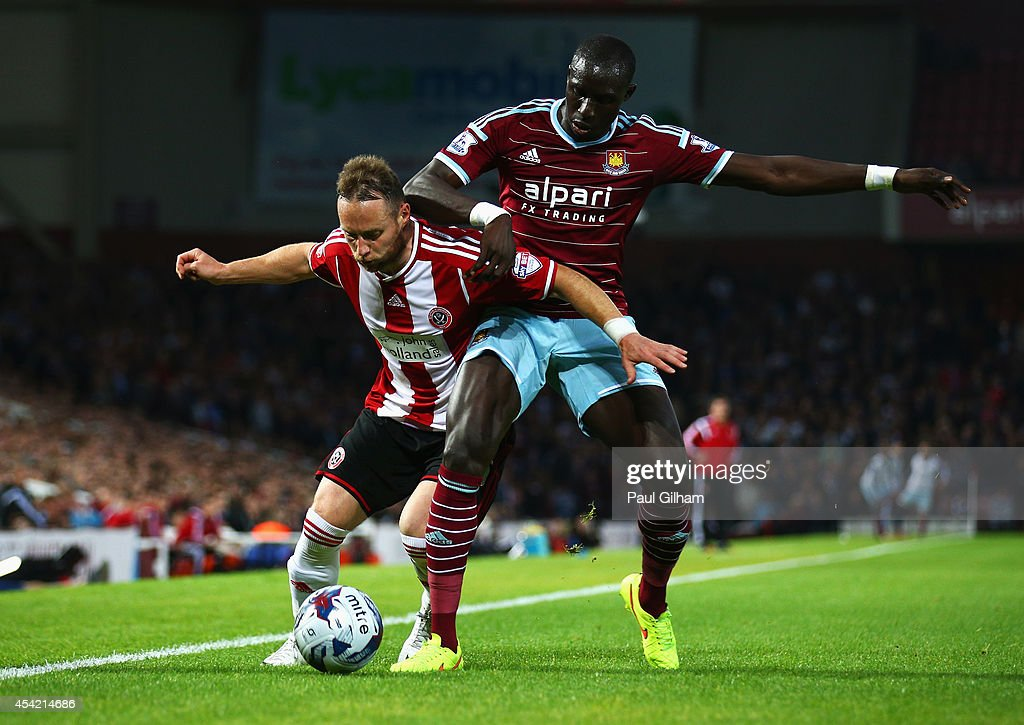 Mohamed Diame of West Ham United challenges Ben Davies of Sheffield United during the Capital One Cup Second Round match between West Ham United and Sheffield United at Boleyn Ground on August 26, 2014 in London, England.