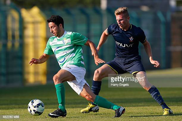 Mohamed El Idrissi of KSK Hasselt avoids the tackle of Jason McCarthy of Southampton during the preseason friendly match between KSK Hasselt and...