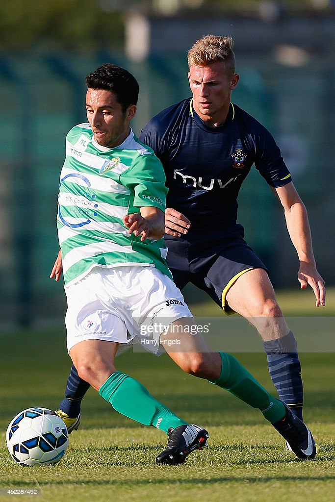 Mohamed El Idrissi of KSK Hasselt avoids the tackle of Jason McCarthy of Southampton during the pre-season friendly match between KSK Hasselt and Southampton at the Stedelijk Sportstadion on July 17, 2014 in Hasselt, Belgium.