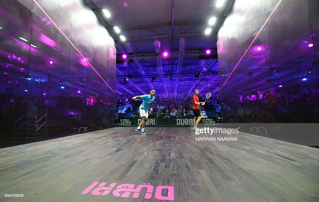 Mohamed El Shorbagy of Egypt (L) plays a backhand to Cameron Pilley of Australia during their semi-final match of the Dubai PSA World Series Finals squash tournament in Dubai on May 27, 2016. / AFP / MARWAN