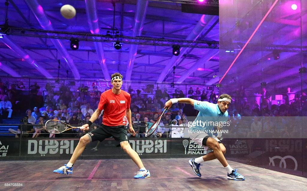 Mohamed El Shorbagy of Egypt (R) plays a backhand to Cameron Pilley of Australia during their semi-final match of the Dubai PSA World Series Finals squash tournament in Dubai on May 27, 2016. / AFP / MARWAN