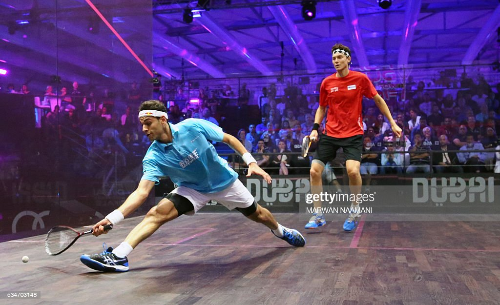 Mohamed El Shorbagy (L) of Egypt plays a forehand to Cameron Pilley of Australia during their semi-final match of the Dubai PSA World Series Finals squash tournament in Dubai on May 27, 2016. / AFP / MARWAN