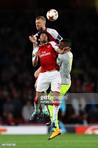 Mohamed Elneny of Arsenal and Per Mertesacker of Arsenal are challenged by Jhon Cordoba of FC Koeln during the UEFA Europa League group H match...