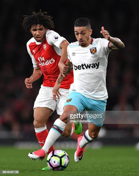 Mohamed Elneny of Arsenal puts pressure on Manuel Lanzini of West Ham United during the Premier League match between Arsenal and West Ham United at...