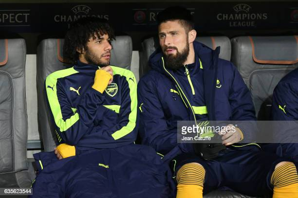 Mohamed Elneny talks to Olivier Giroud of Arsenal on the bench during the UEFA Champions League Round of 16 first leg match between FC Bayern...