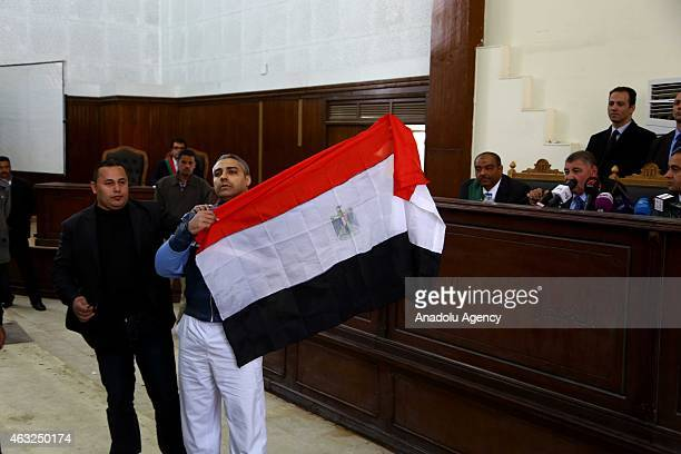 Mohamed Fahmy journalists from Qatar's Al Jazeera television network unfurls Egyptian flag during the hearing at police academy in Cario Egypt on...