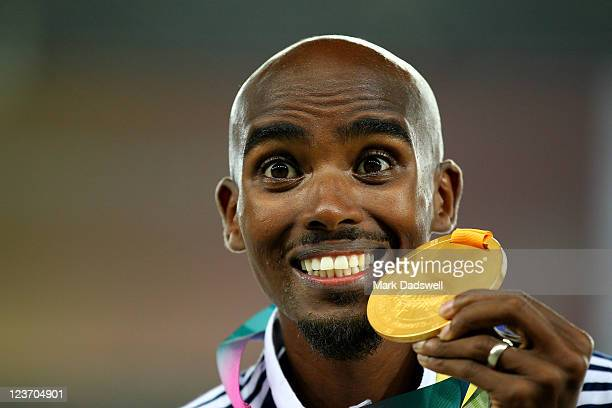 Mohamed Farah of Great Britain celebrates with his gold medal during the medal ceremony for the men's 5000 metres final during day nine of 13th IAAF...