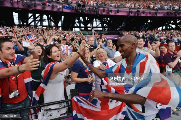 Mohamed Farah of Great Britain celebrates with the crowd after winning gold in the Men's 5000m Final on Day 15 of the London 2012 Olympic Games at...