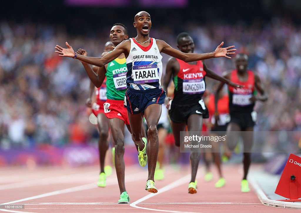 Mohamed Farah of Great Britain crosses the finish line to win gold ahead of <a gi-track='captionPersonalityLinkClicked' href=/galleries/search?phrase=Dejen+Gebremeskel&family=editorial&specificpeople=5857672 ng-click='$event.stopPropagation()'>Dejen Gebremeskel</a> of Ethiopia and <a gi-track='captionPersonalityLinkClicked' href=/galleries/search?phrase=Thomas+Pkemei+Longosiwa&family=editorial&specificpeople=5501347 ng-click='$event.stopPropagation()'>Thomas Pkemei Longosiwa</a> of Kenya in the Men's 5000m Final on Day 15 of the London 2012 Olympic Games at Olympic Stadium on August 11, 2012 in London, England.