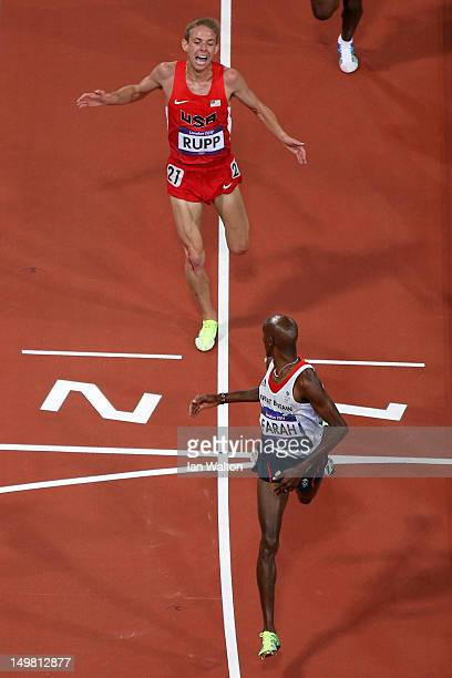 Mohamed Farah of Great Britain looks back to Galen Rupp of the United States as he crosses the line to win gold in the Men's 10000m Final on Day 8 of...