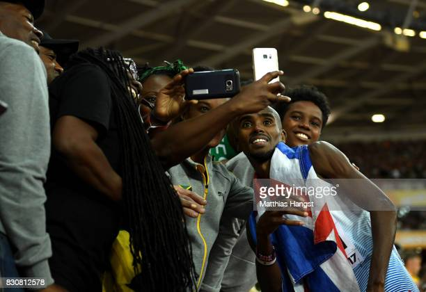Mohamed Farah of Great Britain poses for selfies with fans as he walks off the track after finishing second in the Men's 5000 Metres final during day...