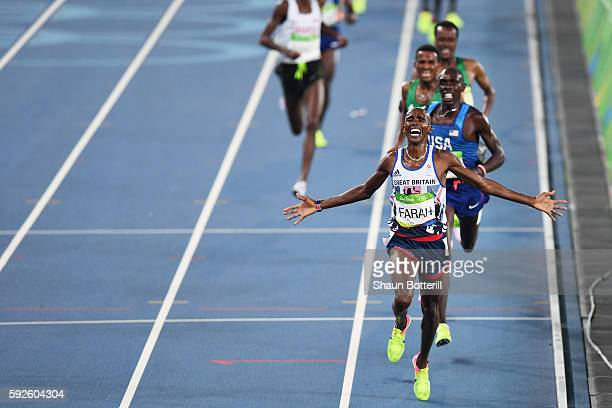 Mohamed Farah of Great Britain reacts after winning gold in front of Paul Kipkemoi Chelimo of the United States in the Men's 5000 meter on Day 15 of...