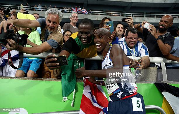 Mohamed Farah of Great Britain takes a photo after winning gold in the Men's 5000 meter Final on Day 15 of the Rio 2016 Olympic Games at the Olympic...