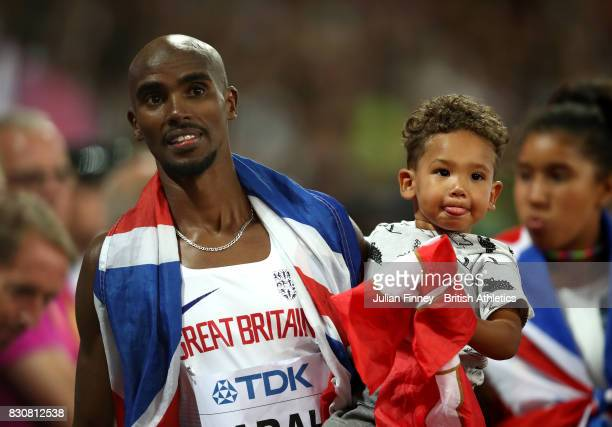 Mohamed Farah of Great Britain with his son Hussein he walks off the track after finishing second in the Men's 5000 Metres final during day nine of...