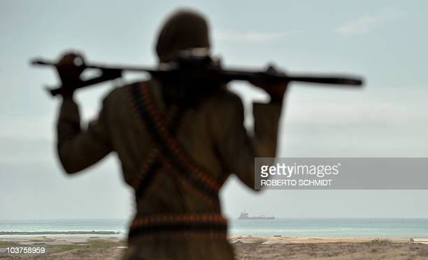 Mohamed Garfanji Somalia's top pirate boss stands on sandy dunes just outside the central Somali coastal town of Hobyo as he watches the outline of a...