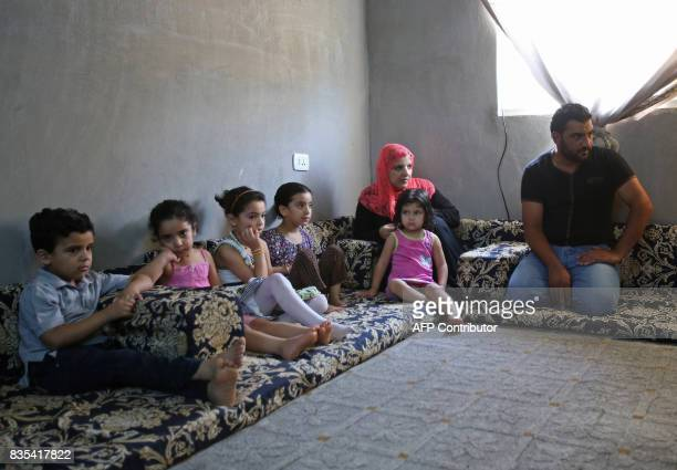 Mohamed Ghazal a Syrian refugee sits with his family on August 9 in a home in the northern Jodanian town of Irbid where they are being housed under a...