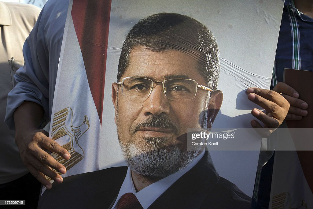 Mohamed Morsi is pictured on a poster as members of the Muslim Brotherhood and supporters of ousted president Mohamed Morsi at a rally outside Rabaa al-Adawiya mosque on July 15, 2013 in Cairo, Egypt. Senior US official William Burns has arrived in Egypt for the first time since the overthrow of Mohamed Morsi.