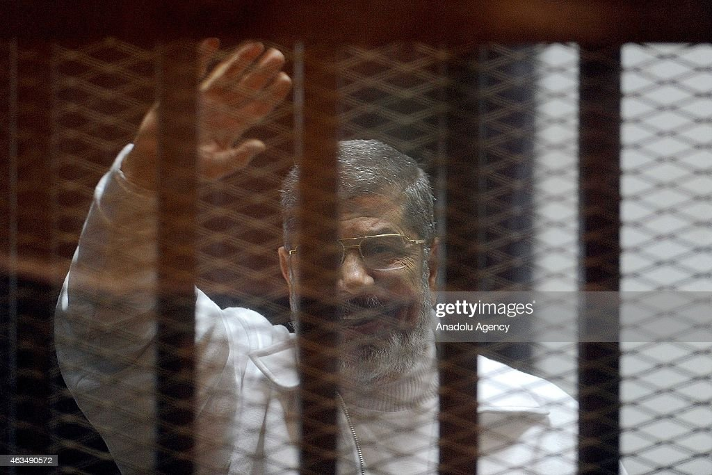 Mohamed Morsi stands inside a glass defendant's cage during first session in the trial where Morsi and 10 other co-defendants face on charges of spying for Qatar, the Gulf ally to the Morsi administration, in Cairo, Egypt on February 15, 2015.