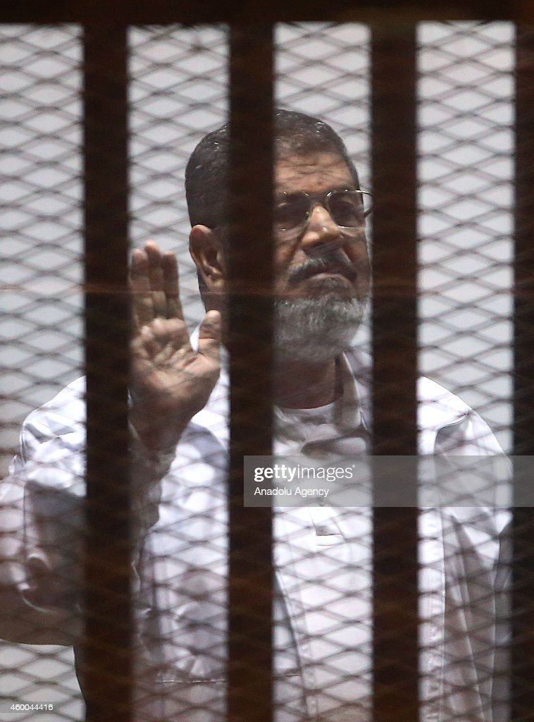 Mohamed Morsi stands inside a glass defendant's cage during his trial at Police Academy in the east of Cairo, Egypt, on December 6, 2014. Morsi and his 35 other co-defendants are accused of being spy.