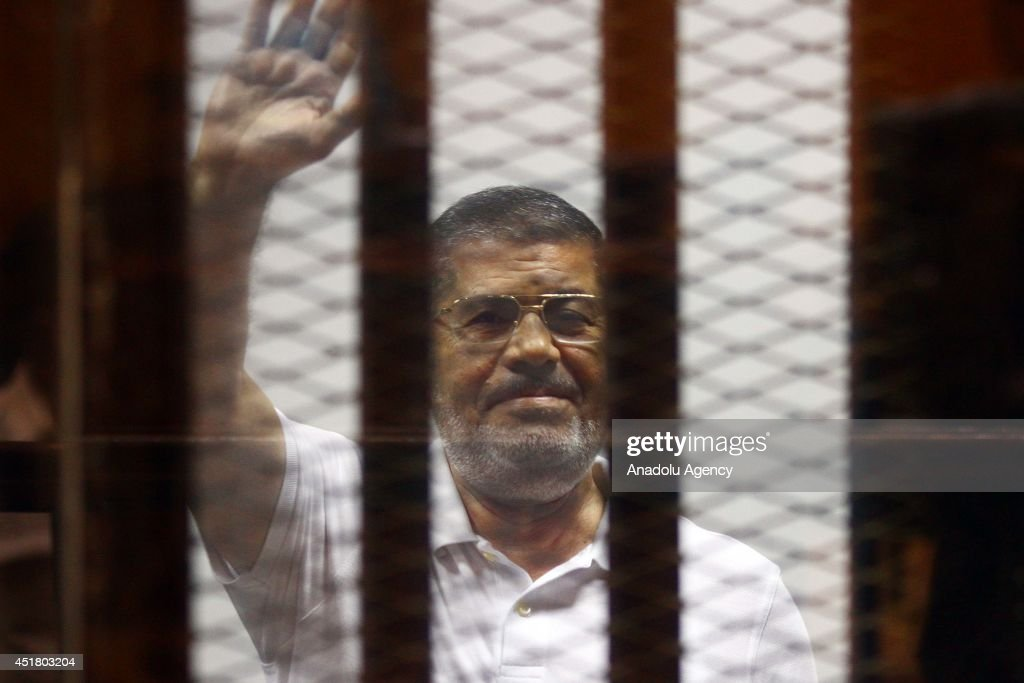 Mohamed Morsi waves as he stands inside a glass defendant's cage during his trial in Cairo Egypt on July 07 2014 An Egyptian court on Monday...
