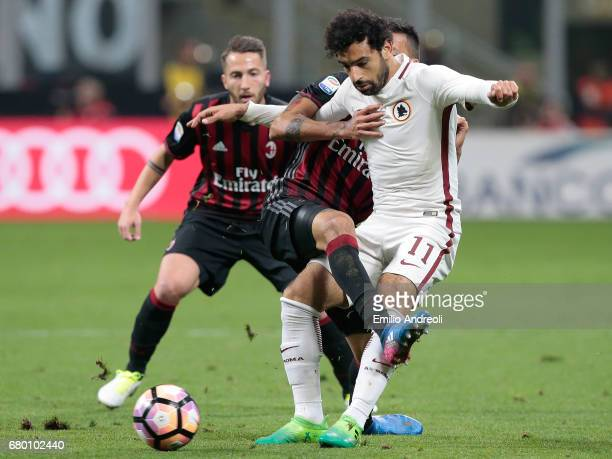 Mohamed Salah of AS Roma competes for the ball with Leonel Vangioni of AC Milan during the Serie A match between AC Milan and AS Roma at Stadio...