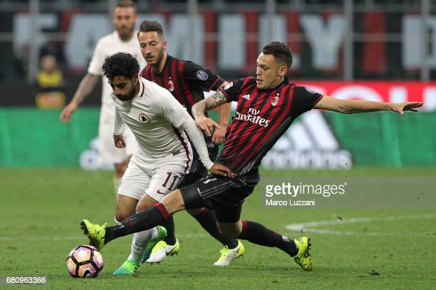 Mohamed Salah of AS Roma is challenged by Lucas Ocampos of AC Milan during the Serie A match between AC Milan and AS Roma at Stadio Giuseppe Meazza...