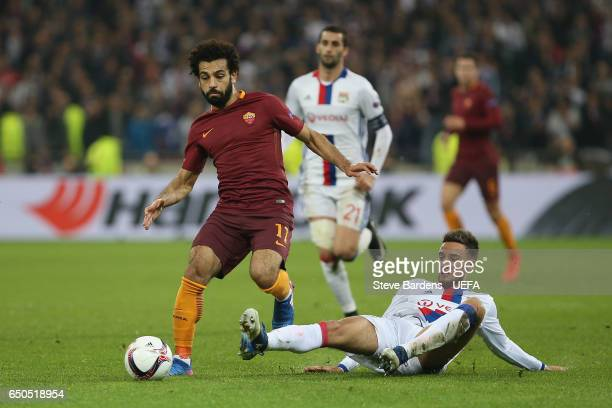 Mohamed Salah of AS Roma is tackled by Emanuel Mammana of Olympique Lyon during the UEFA Europa League Round of 16 first leg match between Olympique...