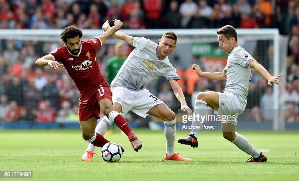 Mohamed Salah of Liverpool competes with Memanja Matic and Ander Herrera of Manchester United during the Premier League match between Liverpool and...
