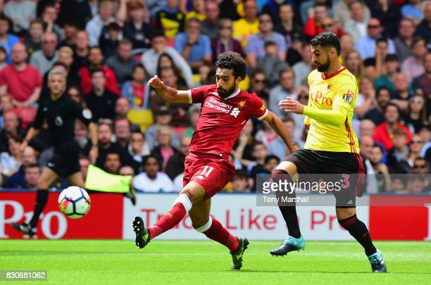 Mohamed Salah of Liverpool shoots as Miguel Britos of Watford attempts to block during the Premier League match between Watford and Liverpool at...