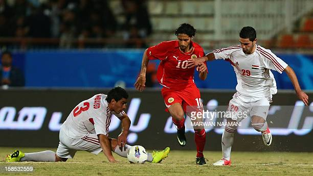 Mohamed Salmeen of Bahrain dribbles the ball between Omar Khrbin and Samer Awad of Syria during their semifinal football match in the 7th West Asia...