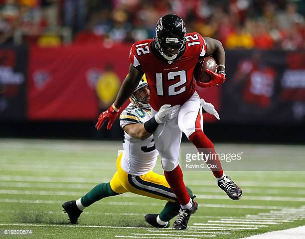Mohamed Sanu of the Atlanta Falcons attempts to break a tackle by Micah Hyde of the Green Bay Packers at Georgia Dome on October 30 2016 in Atlanta...