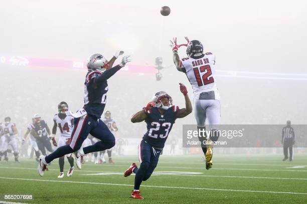 Mohamed Sanu of the Atlanta Falcons catches a pass as he is defended by Patrick Chung of the New England Patriots during the fourth quarter of a game...