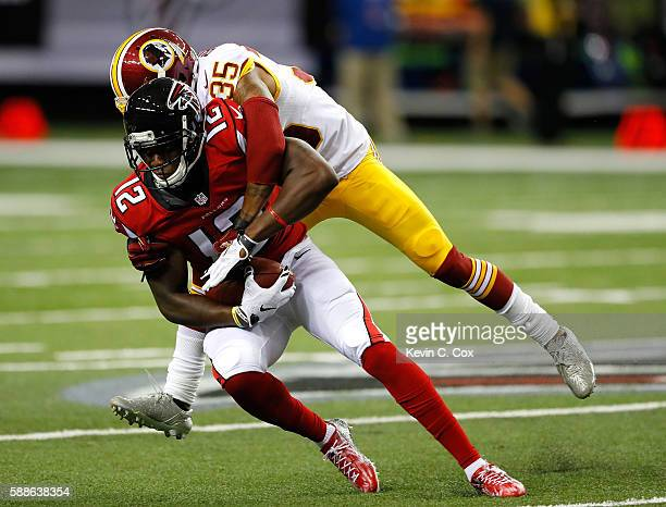 Mohamed Sanu of the Atlanta Falcons is tackled by Dashaun Phillips of the Washington Redskins at Georgia Dome on August 11 2016 in Atlanta Georgia