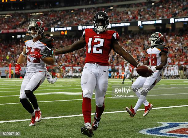 Mohamed Sanu of the Atlanta Falcons scores a twopoint conversion against Chris Conte and Jude AdjeiBarimah of the Tampa Bay Buccaneers at Georgia...