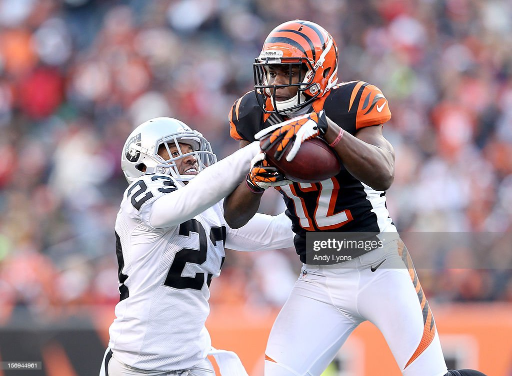 Mohamed Sanu #12 of the Cincinnati Bengals catches a pass while defended by Joselio Handon #23 of the Oakland Raiders during the NFL game at Paul Brown Stadium on November 25, 2012 in Cincinnati, Ohio.