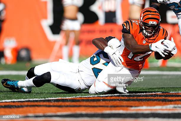 Mohamed Sanu of the Cincinnati Bengals dives into the end zone past JT Thomas of the Jacksonville Jaguars to score a touchdown during the second...